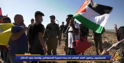 فلسطينيون يرفعون العلم الوطني في وجه مسيرة للمستوطنين يؤمنها جنود الاحتلال